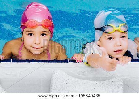 Cute children in the swimming pool on indoor swimming pool toned image