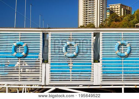 Blue lifebuoy hanging on wooden wall beach tent on shore of a pebbly coast in resort city Sochi. Relaxing beach vacation in coastal summer tent. Architecture of modern resort town. Krasnodar Russia