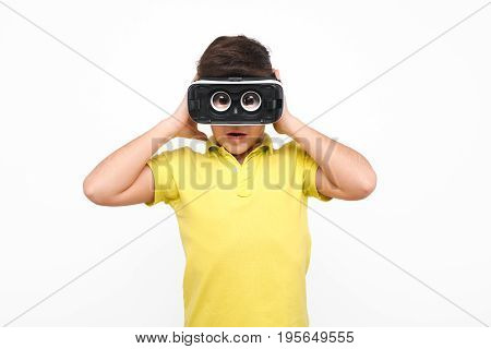 Little boy in casual clothing wearing VR goggles and looking excited on white background.