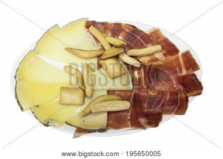 Plate with spanish cheese and serrano ham isolated on white background