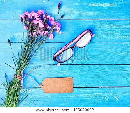 Bouquet of field carnations with a paper tag and glasses on a blue wooden background