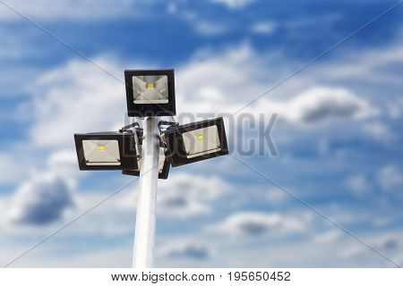 Street LED Light with energy-saving technology on the pole against blurred blue cloudy sky