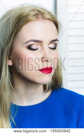 Girl with closed eyes red lips and professional makeup on adorable face posing in blue dress. Woman with long blond hair on white background. Visage cosmetics skincare make up. Beauty youth