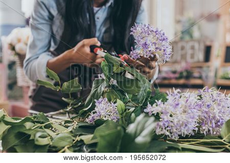Close-up Partial View Of Florist Cutting Flowers With Secateurs
