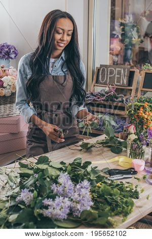 Beautiful Smiling African American Woman In Apron Holding Secateurs And Working With Fresh Plants In