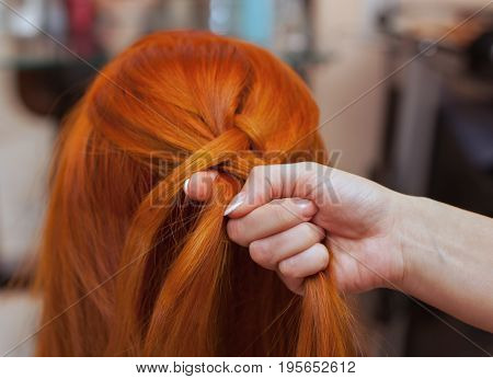 Beautiful Girl With Red Long Hair, Hairdresser Weaves A French Braid, In A Beauty Salon. Professiona