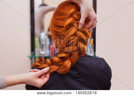 Beautiful, Red-haired Girl With Long Hair, Hairdresser Weaves A French Braid, In A Beauty Salon. Pro