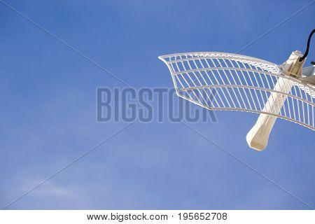 Internet antenna dish against a blue sky
