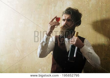 Man With Bottle Looking At Red Wine In Glass