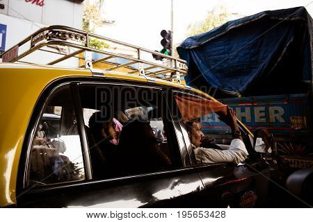 MUMBAI, INDIA - November 5 2017: A taxi driver and his passenger wait in heavy traffic in downtown Mumbai, India