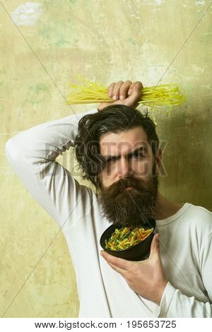 Man with pasta in hand. Healthy food and dieting. Cooking raw spaghetti in restaurant. Cook or chef bearded man with bowl. Hipster hold Italian macaroni.