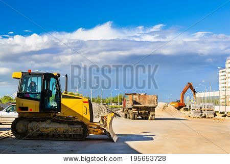 Crawler tractor with bucket on construction of high-speed ring road around Krasnoe Selo Saint Petersburg. Heavy machine equipment for excavation works at civil industrial construction. Russia