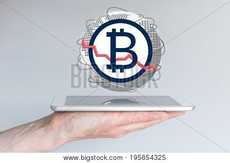 Decline of global bitcoin currency exchange rate concept with hand holding tablet