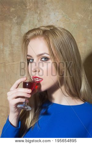 Woman drinking glass of red liqueur. Girl with blond long hair make up in blue dress on beige wall. Alcohol appetizer bad habits addictive and convive. Unhealthy lifestyle