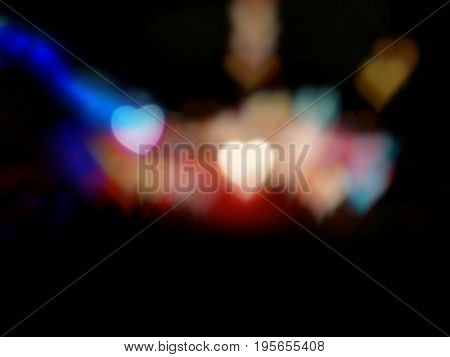 Abstract blur light of two hearts among colorful heart bokeh on black background; taken from colorful flashlights decorated on trees at night - Bottom copy space. Concepts of love and valentine.
