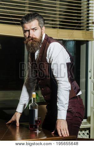 Hipster Standing At Table With Bottle And Glass Of Wine