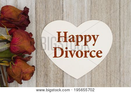 Happy divorce message Dead red roses with heart-shape card on weathered wood background with text Happy Divorce