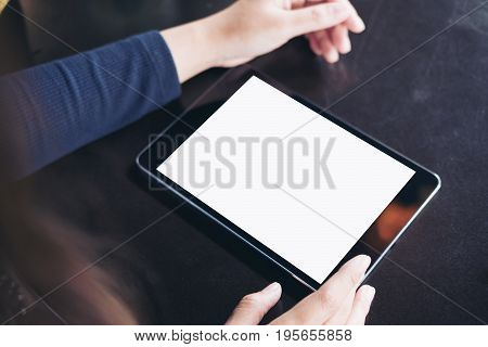 Mockup image of hands using a black tablet pc with blank white screen on vintage black table background
