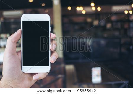 Mockup image of hand holding white mobile phone with blank black screen in cafe