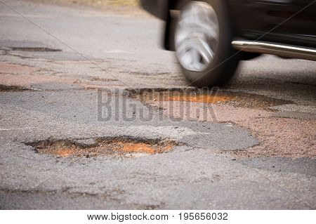 Rear wheel of a moving car about to drive into a pothole
