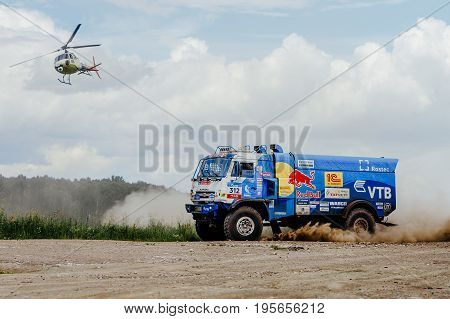 Filimonovo Russia - July 10 2017: truck rally truck KAMAZ on dust road with a flying helicopter during Silk way rally
