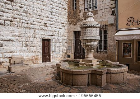 Vence, France - July 14, 2016. View of wall, fountain and shop in Vence, a stunning medieval town completely preserved. In Alpes-Maritimes department, Provence region, southeastern France