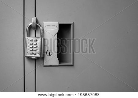 Closeup padlock with key number hanging on locker for concept technology data log security on black and white.