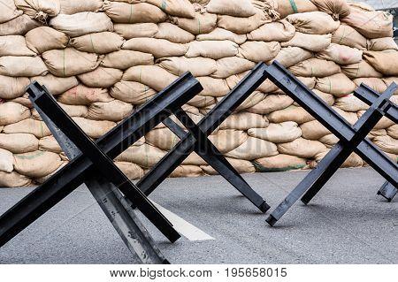 Black steel street barrier in shape of anti-tank Czech hedgehog obstacle defense stands on asphalt urban road