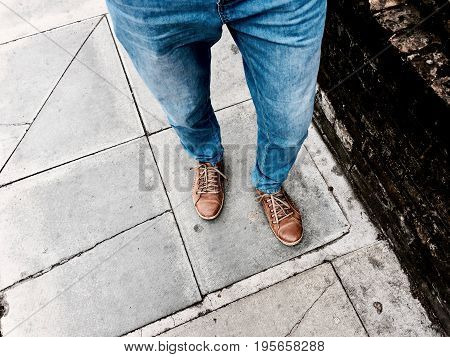 Man in blue jeans and brown shoes on the footpath near brick wall.