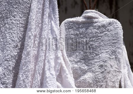 Many Wet towels drying on Window Wrought Iron