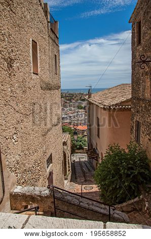 Alley with houses, staircase on the slope and blue sky in Haut-de-Cagnes, a pleasant village on top of a hill, near Nice. In the Alpes-Maritimes department, Provence region, southeastern France.