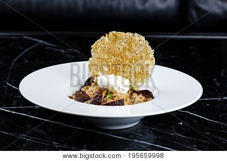 risotto with truffles served in the white plate on the black background