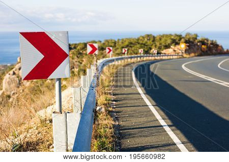 Right Turn Sign: Road signs warn of a sharp turn on a narrow road.