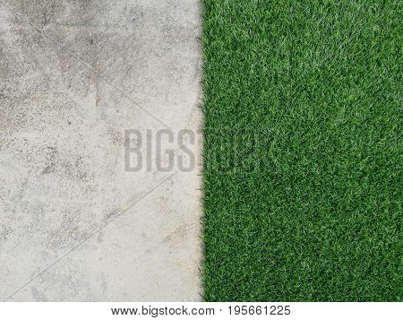 a half of  green artificial grass and gray cement floor, concept is comparison between  green of forest and gray of building  in city .