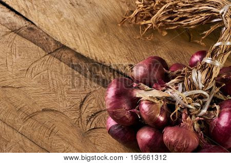 A lot of onions on wooden table. Heap of onions on a old rustic wooden board. Fresh red Onion on wooden background with copy space. Vegetables for healthy nutrition.