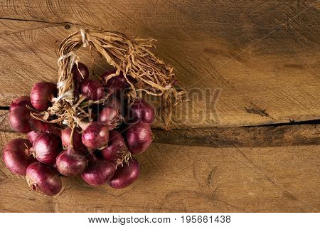 A lot of heads bulb onion on wooden table. Top view of large fresh red onions on a wooden background with copy space. Bunch onions on a old rustic wooden board to prepare meals. Bulb onion is good for health.