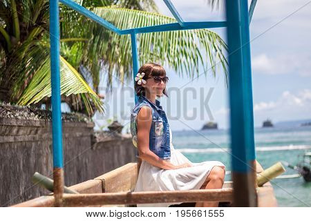 Portrait Young beautiful tropical woman on summer vacation in asia. Relaxing on tropical beach, sea landscape and gree tropical background, slim tanned body, travel alone, short hair.