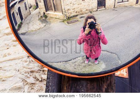 A beautiful woman taking selfie in traffic mirror.