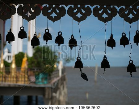 Silhouettes of bells attached to the walkway to Wat Hong Thong by visitors for good luck. The temple is built on a concrete platform at the coast of Chachoensao in Thailand after the sea started to reclaim the area of the original temple several decades a