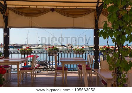 Outdoor restaurant overlooking the marina for yachts and pleasure boats in the resort town of Balchik.