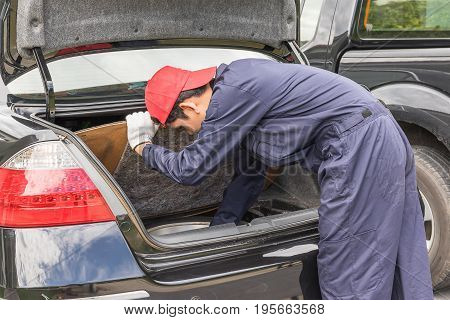 Mechanic Replacing To The Spare Tire At The Back Of The Car