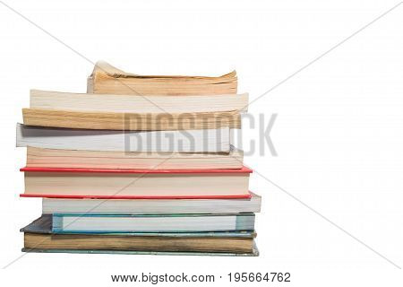 Pile of old used books with one having dog-ears isolated on white with some copy-space on right