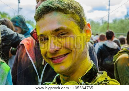 Moscow, Russia - June 3, 2017: Portrait of smiling teenage boy in yellow paint after headshot at summer Holly Colors Festival. Traditional Indian festival turned into fun event in many countries