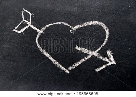 White chalk drawing in heart with arrow shape on black board background use for decoration in valentine love couple or engagement concept