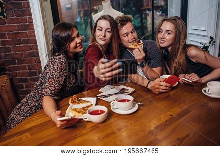 Cheerful students hanging out in a cafe taking photo with phone while having dinner together.