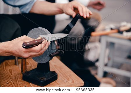 master sharpens the knife by tradition on a hand grindstone. Concept is an old craft, with your own hands.