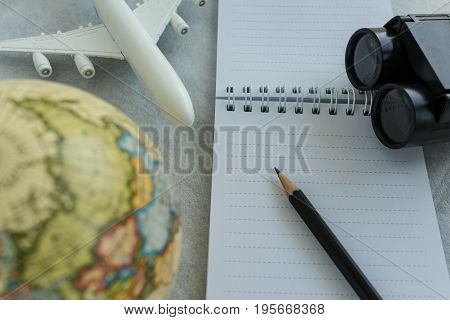 World travel concept with pencil on white note paper toy airplane small globe and binoculars on white background.