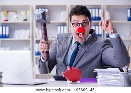 Clown businessman with a piggy bank and a hammer