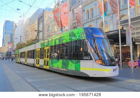 MELBOURNE AUSTRALIA - JULY 7, 2017: Modern tram runs in Melbourne downtown. Melbourne has the largest urban tramway network in the world ahead of St Petersburg.