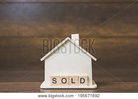 House model with Sold word on wooden blocks. Home finance concept